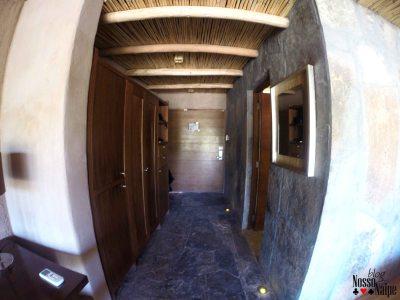 Do lado esquerdo fica o guarda-roupa, o mini bar e o cofre. Do lado direito um espelho e a porta para o banheiro.